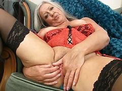 Mature lady April Thomas in black stockings and red lingeries teasing her old pussy